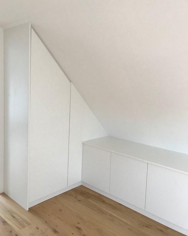 Weißer Einbauschrank in Dachschräge mit seitlichem Sideboard